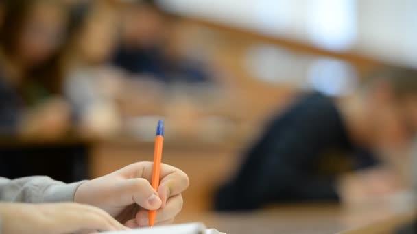 A diákok az egyetemen (iskola) az osztályteremben. Jegyzetfüzet, tollak, közel kezekkel.