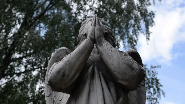 Postava anděla na náhrobek (památka) na hřbitově proti modré obloze