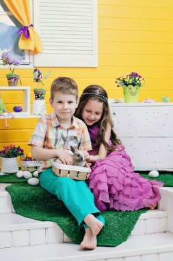 Happy children play with a rabbit. a boy and a girl in a bright room laugh and play