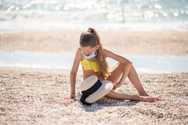 Beautiful girl alone on the beach in a medical mask. A crisis. How to wear a mask when traveling. Family content. Child isolated on the beach. Keep your distance. Beautiful long-haired girl in a swimsuit on the ocean