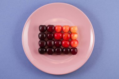Multicolored cherry berries on a pink bowl on a blue background.