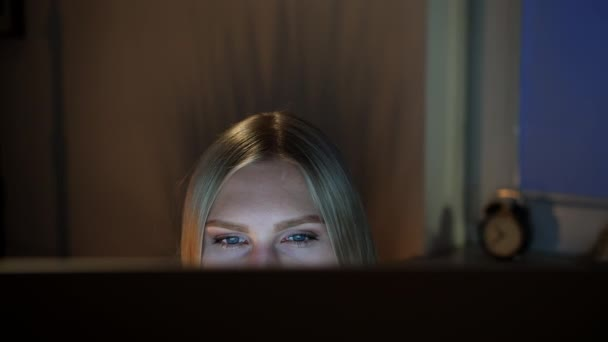 Crop view of beautiful female sitting at night at computer and looking at camera over top of monitor with dark window on blurred background