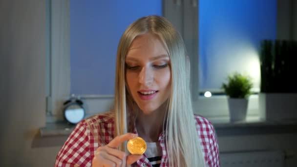 Šťastná žena držící bitcoin ukazuje palec nahoru. Veselá mladá blond žena v neformálním oblečení sedí u okna v noci držel bitcoin a dělá palec nahoru gesto s úsměvem a při pohledu na fotoaparát