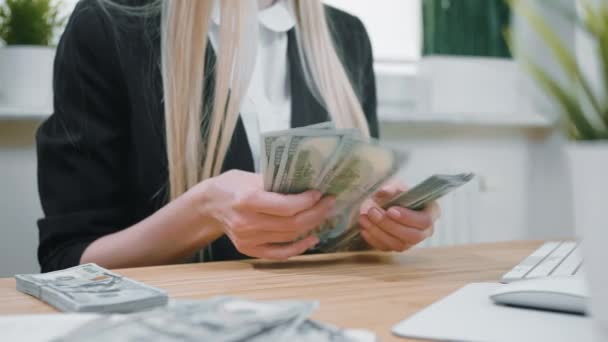 Business woman counting cash in hands. Crop view of female in elegant suit sitting at wooden desk and counting large bundle of dollar banknotes in hands.
