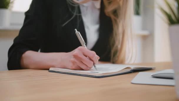 Szép fiatal szőke női ruha ül íróasztal a Jegyzettömb tollal írás, oldal fordítás, és húzza ki a papírt a notebook.