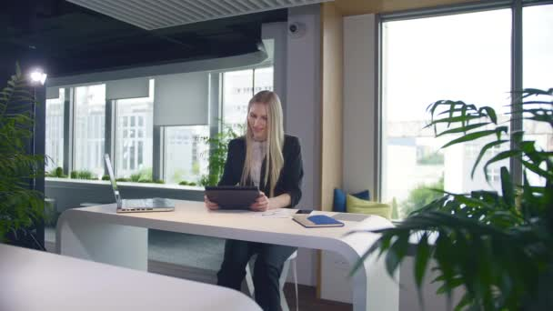 Stylish business woman with tablet in office. Elegant woman in suit sitting at table with laptop and surfing tablet in modern light office with big windows.