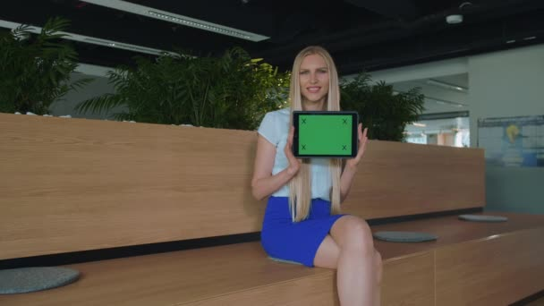 Woman showing tablet in office. Young smiling blond woman showing tablet with green chromakey screen looking at camera and smiling in office.