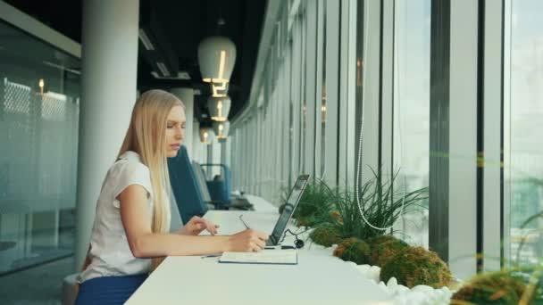 Üzletasszony, aki laptoppal dolgozik az új irodában. Oldalnézet nő ül asztalnál mellett ablak a modern irodában, és használja laptop nappal.