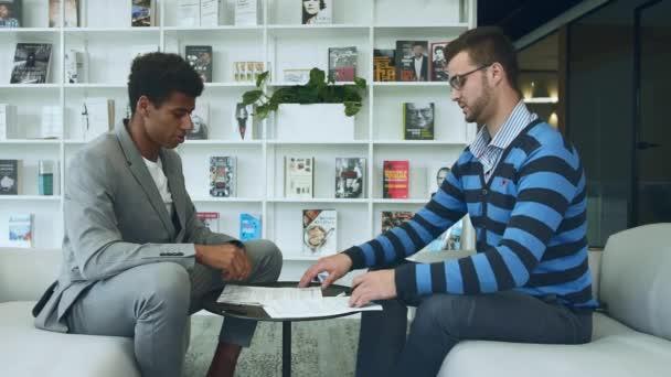Muži dělat dohodu a podepisování dokumentů. Boční pohled na různých mužů, podepsání smlouvy a třást ruce v symbolu dohody sedí na pohovce v kanceláři.