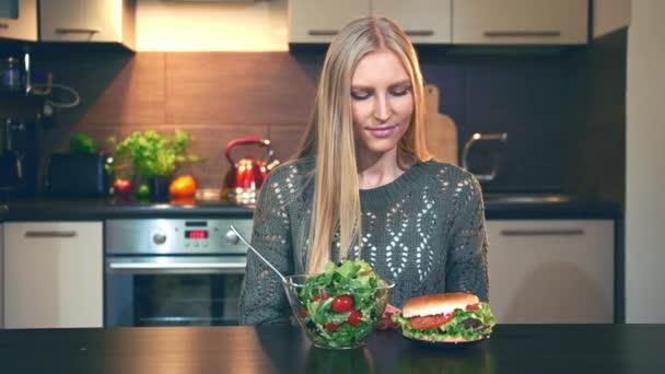 Dívka, raději salát hamburger. Atraktivní mladá žena, pokud se rozhodnete jíst zdravé salát k večeři sedíte u stolu ve stylové kuchyni.