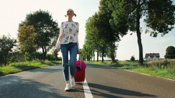 fröhliche junge Frau mit Koffer läuft auf Straße.