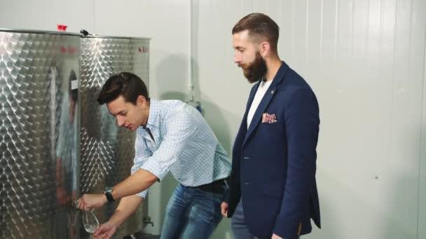 Muži ochutnávka čerstvé víno během výroby