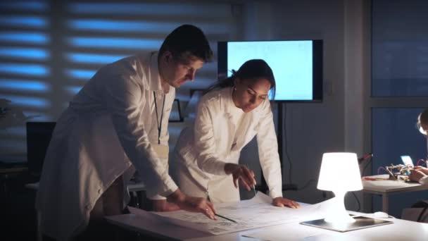 Střední zblízka dva inženýři vývoje elektroniky kontrolující schéma řízení elektroniky v moderní laboratoři