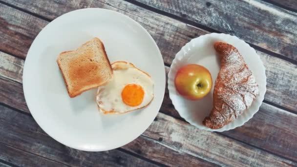 Zdravé chutné snídaně: smažené vejce, toust, jablko a croissant