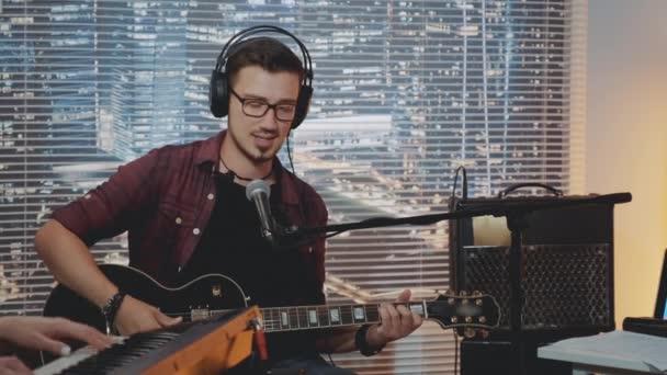 Hudebník ve sluchátkách a módní ležérní oblečení nahrávání jeho nové písně v domácím studiu