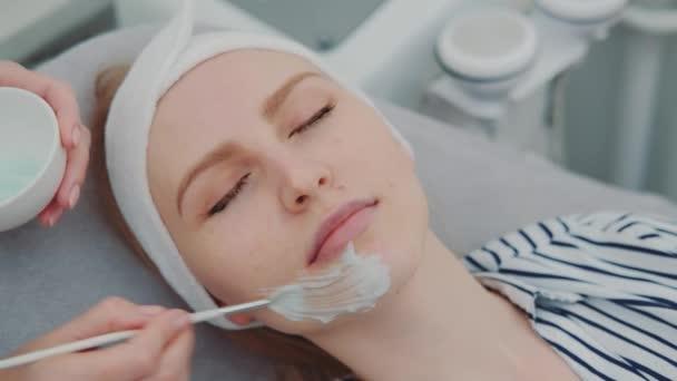 Kosmetikerin trägt im Schönheitssalon Creme-Maske auf das Gesicht junger Frauen auf
