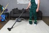 Oříznout záběr člověka pomocí vysavače a čistící bílý koberec