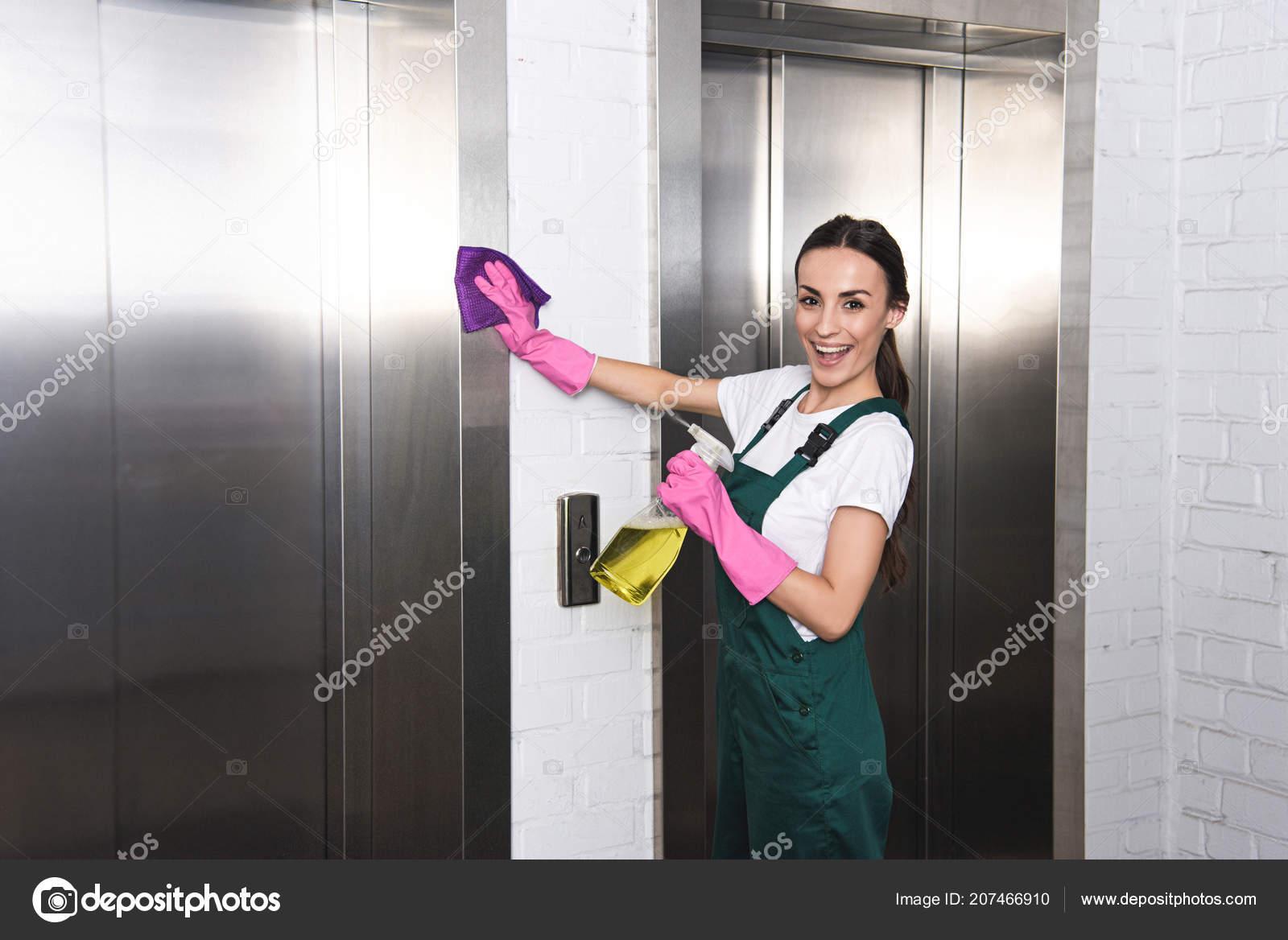 e7ddbec59642 Bella giovane società operaio di pulizia pulizia ascensore e sorride alla  macchina fotografica — Foto di ...