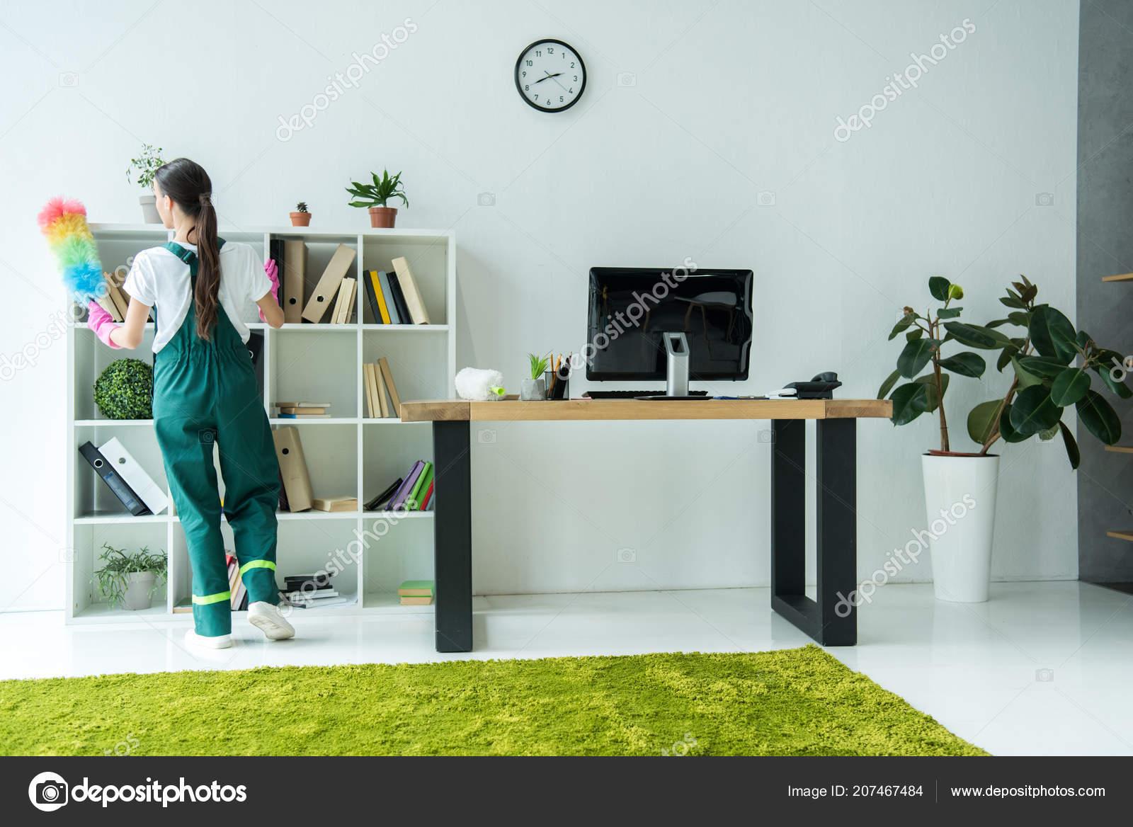 Vue arrière jeune aspirateur tenant duster nettoyage bureaux