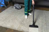 Photo high angle view of professional cleaner using vacuum cleaner and cleaning white carpet