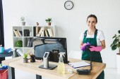 Photo beautiful young professional cleaner smiling at camera while cleaning modern office