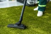 Oříznout záběr osoby čištění zelený koberec s vysavačem