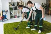 mladá úklidoví pracovníci firmy čištění koberců s vysavačem a pracích prostředků sprej