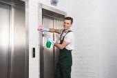 Fényképek csinos fiatal tisztító, mosás, lift és mosolyogva kamera
