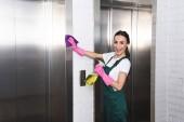 krásná mladá čištění společnosti pracovník čištění výtahu a usmívá se na kameru