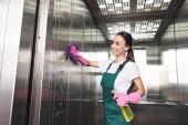 krásné usměvavé mladé čistší mytí výtah s pracího prostředku a hadr