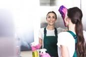 Fotografie s úsměvem mladá žena čistič mytí výtahu s hadr a saponát
