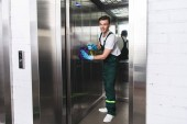 pohledný mladý muž, úklid výtahu a usmívá se na kameru