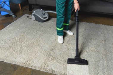 high angle view of professional cleaner using vacuum cleaner and cleaning white carpet