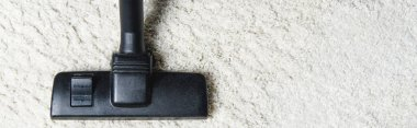 top view of white carpet and vacuum cleaner, close-up view