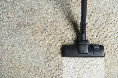 top view of cleaning white carpet with professional vacuum cleaner