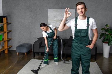 smiling young cleaning company workers using vacuum cleaner and showing ok sign