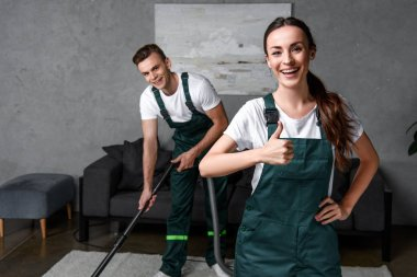 happy young cleaning company workers using vacuum cleaner and showing thumb up