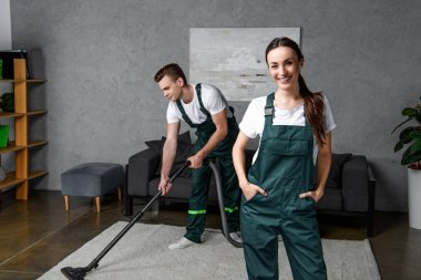 young cleaning company workers using vacuum cleaner and smiling at camera