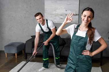 happy young cleaning company workers using vacuum cleaner and showing ok sign