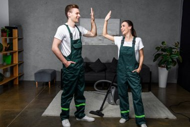 happy young professional cleaners smiling each other and giving high five