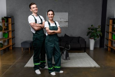 happy young professional cleaners standing with crossed arms and smiling at camera