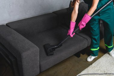 high angle view of woman in rubber gloves cleaning furniture with vacuum cleaner