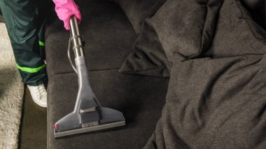 partial view of person in rubber glove cleaning sofa with vacuum cleaner