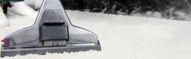 close-up view of hot steam cleaning of white carpet with professional vacuum cleaner