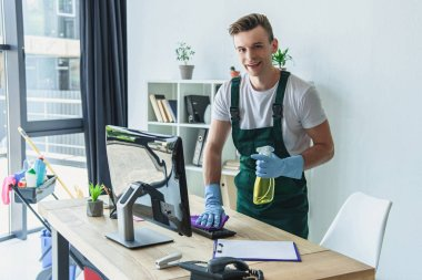 handsome professional cleaner in rubber gloves holding detergent spray and smiling at camera in office