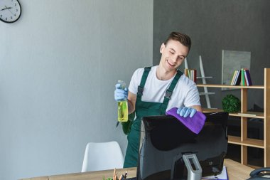 happy young professional cleaner holding rag with detergent and cleaning computer monitor in office