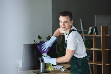 handsome young professional cleaner smiling at camera while cleaning computer monitor in office