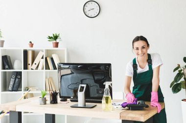 beautiful young cleaner smiling at camera while cleaning table in modern office