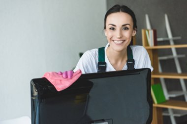 attractive young woman cleaning computer monitor and smiling at camera