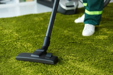 cropped shot of person cleaning green carpet with vacuum cleaner